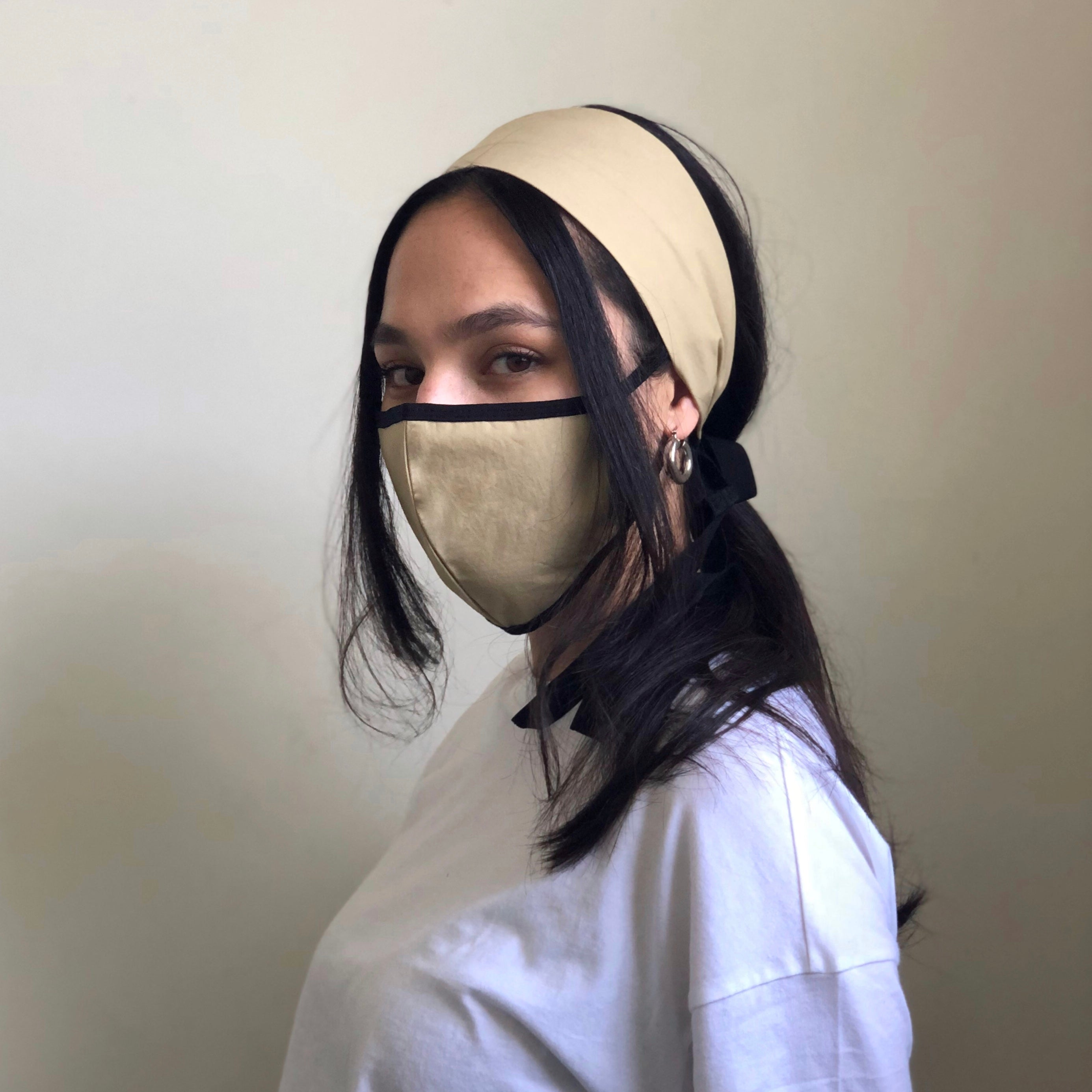 Woman models a sand colored face mask with a matching headband.