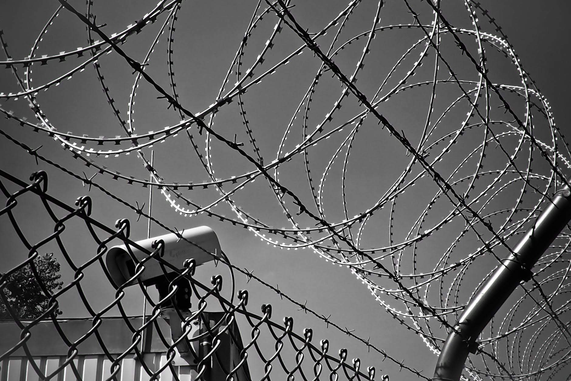 black and white image of barbed wire on fence and security camera