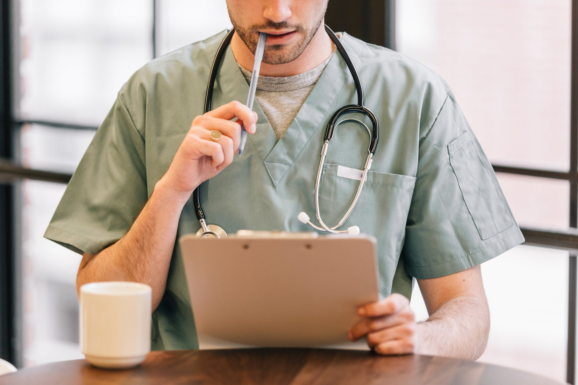 Male RPN in scrubs looking at clipboard