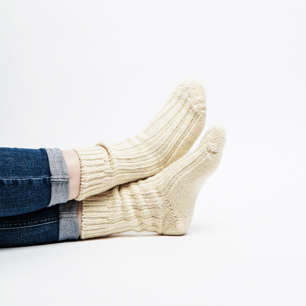 model wears báinín 100% organic wool insulating socks for hiking or lounging data-zoom=
