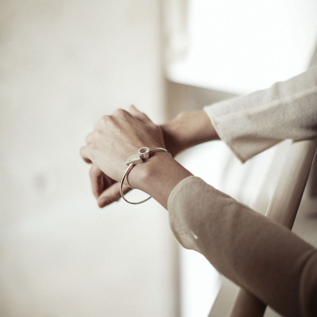 Model wears silver Muriel Bangle with hollow & solid geometric features data-zoom=