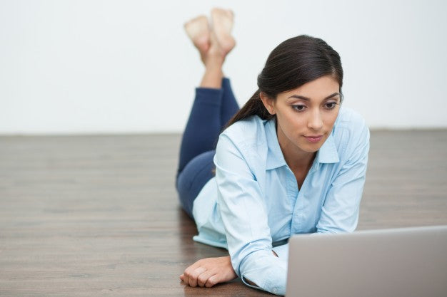 Can You Take CBD Before Work To Enhance Focus? | Blumenes CBD Blog | focused woman on floor looking at laptop