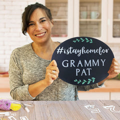 Karen Ardinger Creator of Plata Chalkboards Holding a Oval Plata Chalkboard that says #istayhomefor Grammy Pat