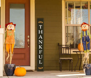 A Plata porch chalkboard stenciled to craft a Thankful Tall Door Sign next to a front door of a colonial home decorated for autumn with scarecrows