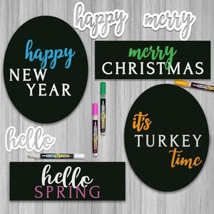 displays 4 Plata Chalkboards decorated using magnetic calligraphy stencils to create holiday signs. Happy New Year Chalkboard Sign, Merry Christmas Wreath Sign, it's Turkey Time Thanksgiving Sign and Hello Spring Wreath Chalkboard Sign by Plata Chalkboards