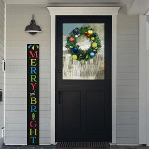 A Plata Porch Chalkboard Christmas Sign stenciled to say Merry and Bright in the front of a home decorated for the holidays