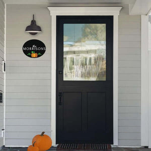 A Plata Oval Holiday Chalkboard Stenciled with a last name and a pumpkin hanging horizontally under a farmhouse light next to front door
