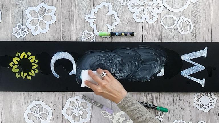 Cleaning the chalkboard with vinegar and eraser sponge to remove chalk paint