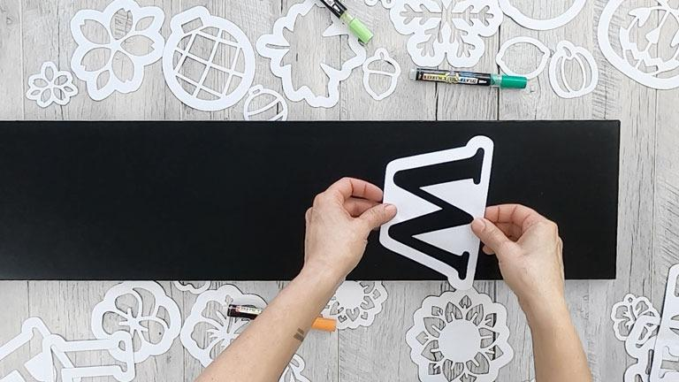 Placing an outdoor W large letter stencil on 5 foot sign to create a DIY Welcome Sign