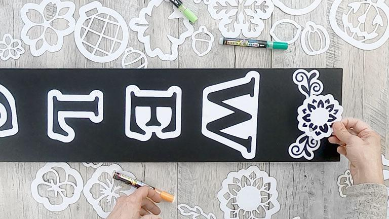 Placing design stencils on a 5 foot sign to create a sunflower welcome sign porch chalkboard