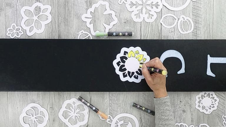 Filling the the sign stencils with painting pens. Shows a sunflower stencil in place of the O in welcome to create a spring summer outdoor welcome sign porch chalkboard