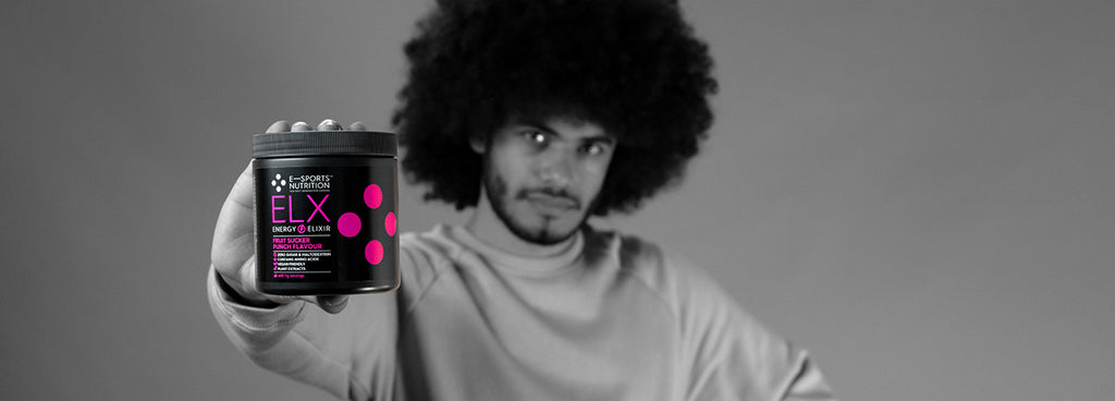 A black and white photo of a male gamer holding a black tub of ELX Energy Elixir Fruit Sucker Punch Flavour