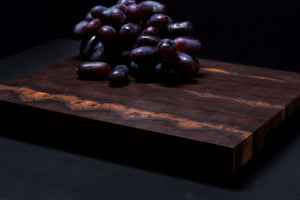 End grain cutting board made of walnut, using the light colored sapwood, against a black background, with vibrant purple grapes on top. Grapes resemble a bow on a gift.