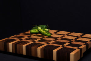 End grain cutting board made of walnut and maple, against a black background, with a vibrant sliced jalepeno on top.