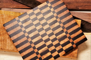 End grain cutting board made of walnut and maple sitting on a pile of rough lumber, from which, this board was hand crafted.