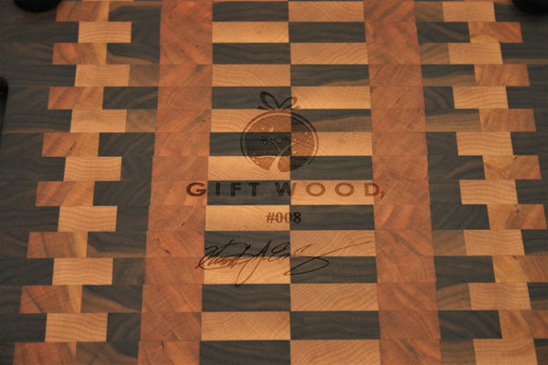 End grain cutting board made of walnut, maple, and cherry, in a zipper-like pattern. The Gift Wood logo, make number, and craftman's signature are engraved on the bottom.