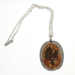 Copper Oval with Copper Leaf Pendant on metal oval Background