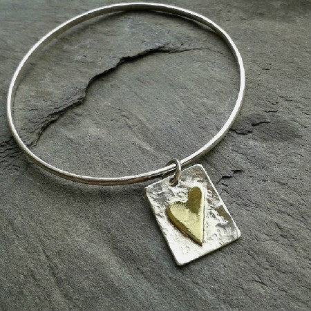 Handmade sterling silver bangle with brass heart tag.