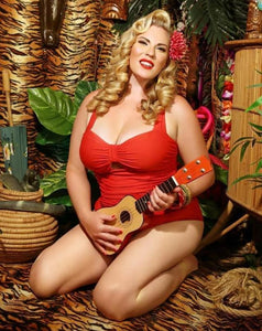 vibrant red 1950s retro vintage style swimsuit with tummy control and ruching modelled by Amy Jones with ukulele
