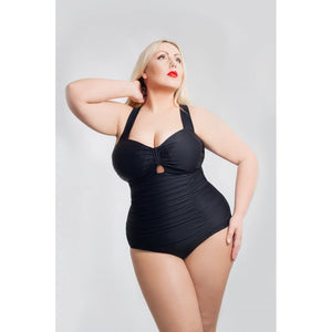 Woman poising in a vintage and retro black swimsuit from the front