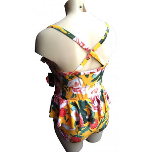 Mustard retro vintage floral swimsuit with ruffle and peplum on mannequin back