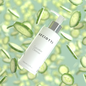 Lots of cucumbers falling in the air with the the hydrating soothing cucumber cleanser with vitamin K & B5 in the middle