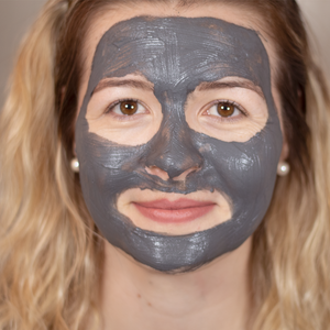 Beautiful lady using the purifying balancing black clay and liquorice face mask