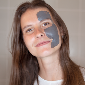 Beautiful lady using the balancing purifying  black clay and liquorice face mask