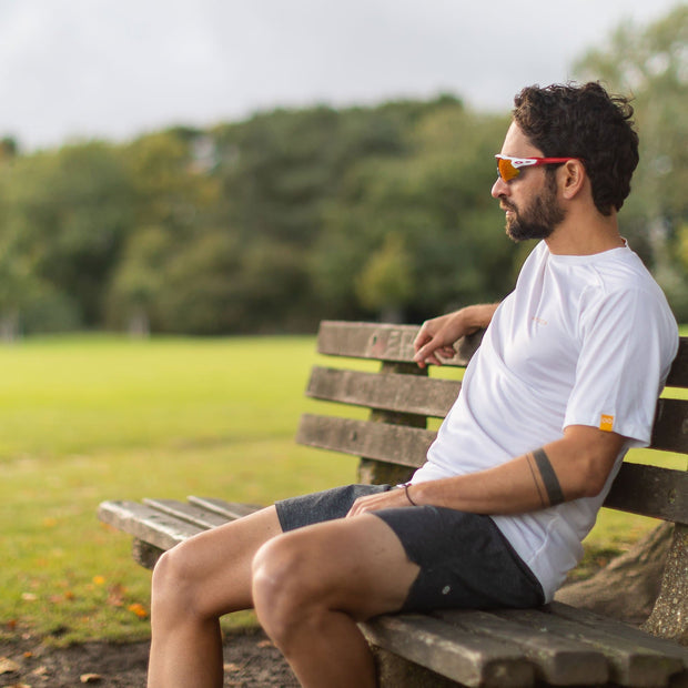 Man On Bench Wearing Tea Male Fully Recycled and Recyclable Sports T-shirt