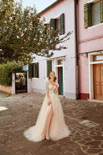This A-line dress features an impeccable embroidered bodice with beaded lace and sheer long sleeves. A slit in the side of the sparkling tulle skirt reveals the leg for a flirty romantic look.