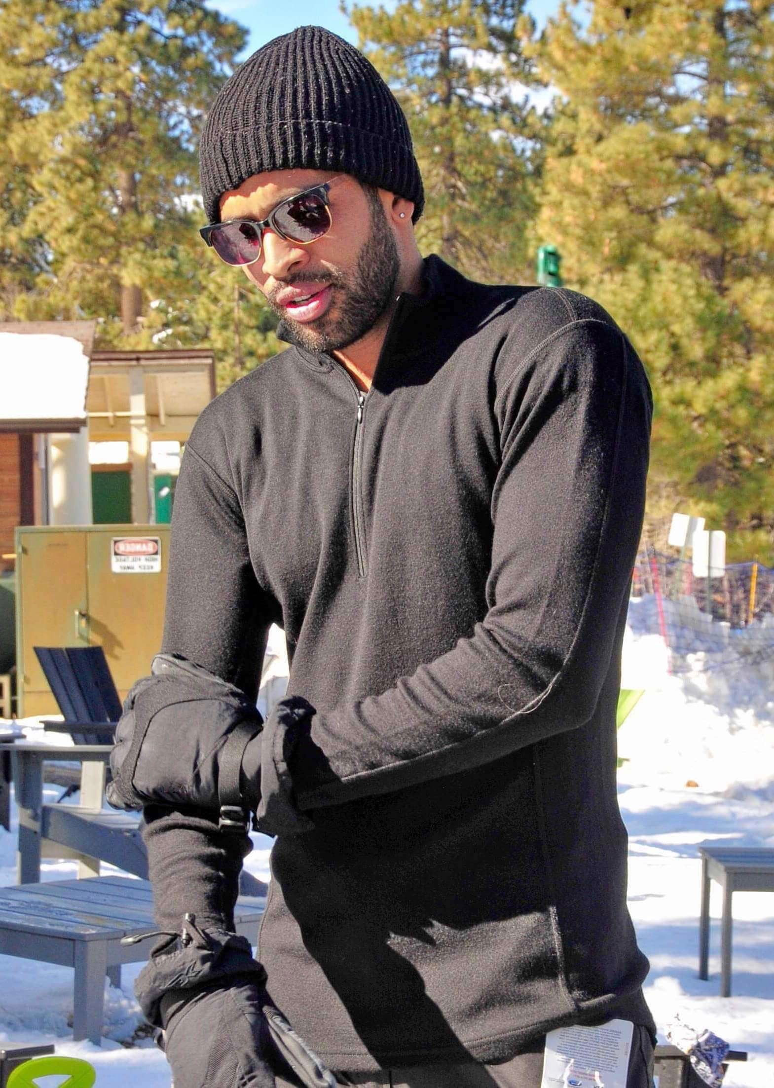 Man wearing black alpaca wool mid layer with half zip and neck in the snow on a sunny day