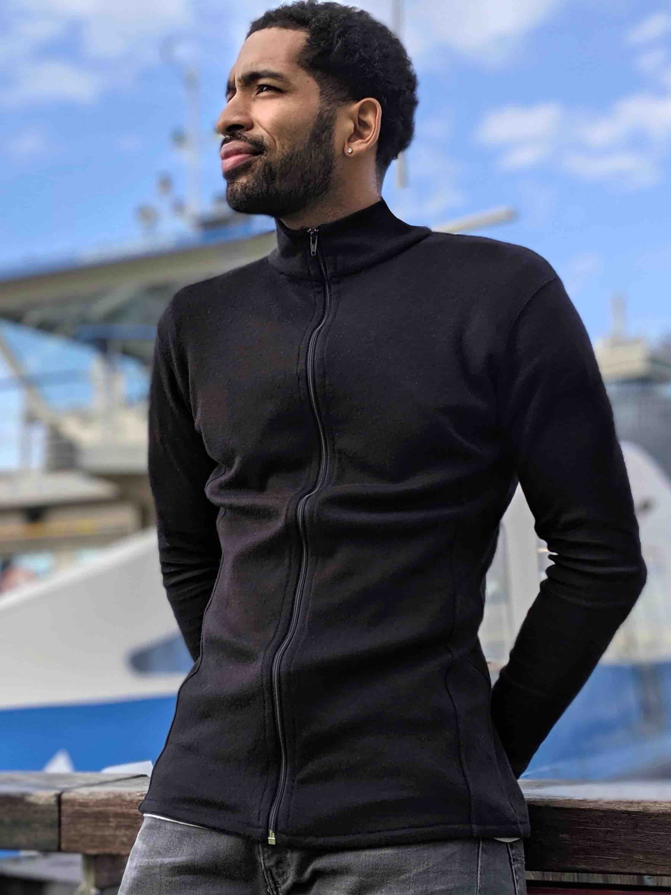 Man wearing a black alpaca wool base layer full zip neck leaning against a port