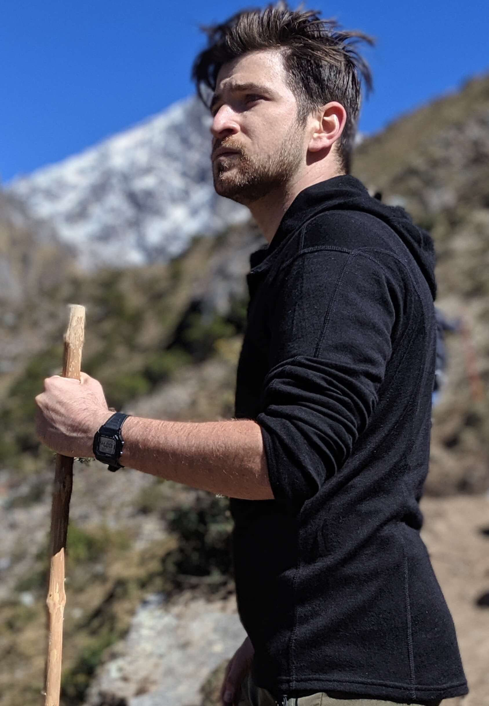 Man with hiking stick wearing black alpaca wool base layer with hoodie