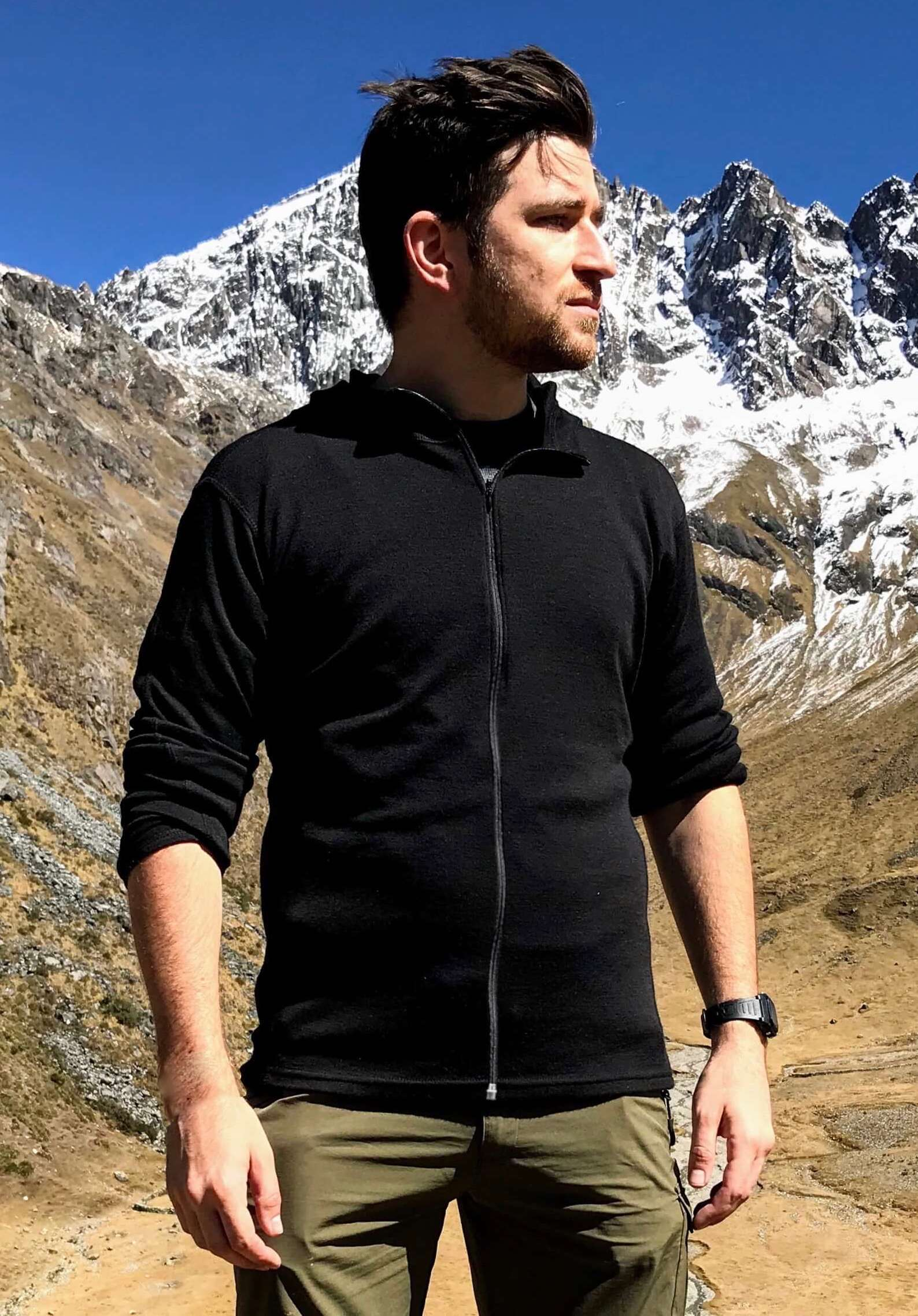 Man wearing alpaca wool base layer with full zip with mountains behind