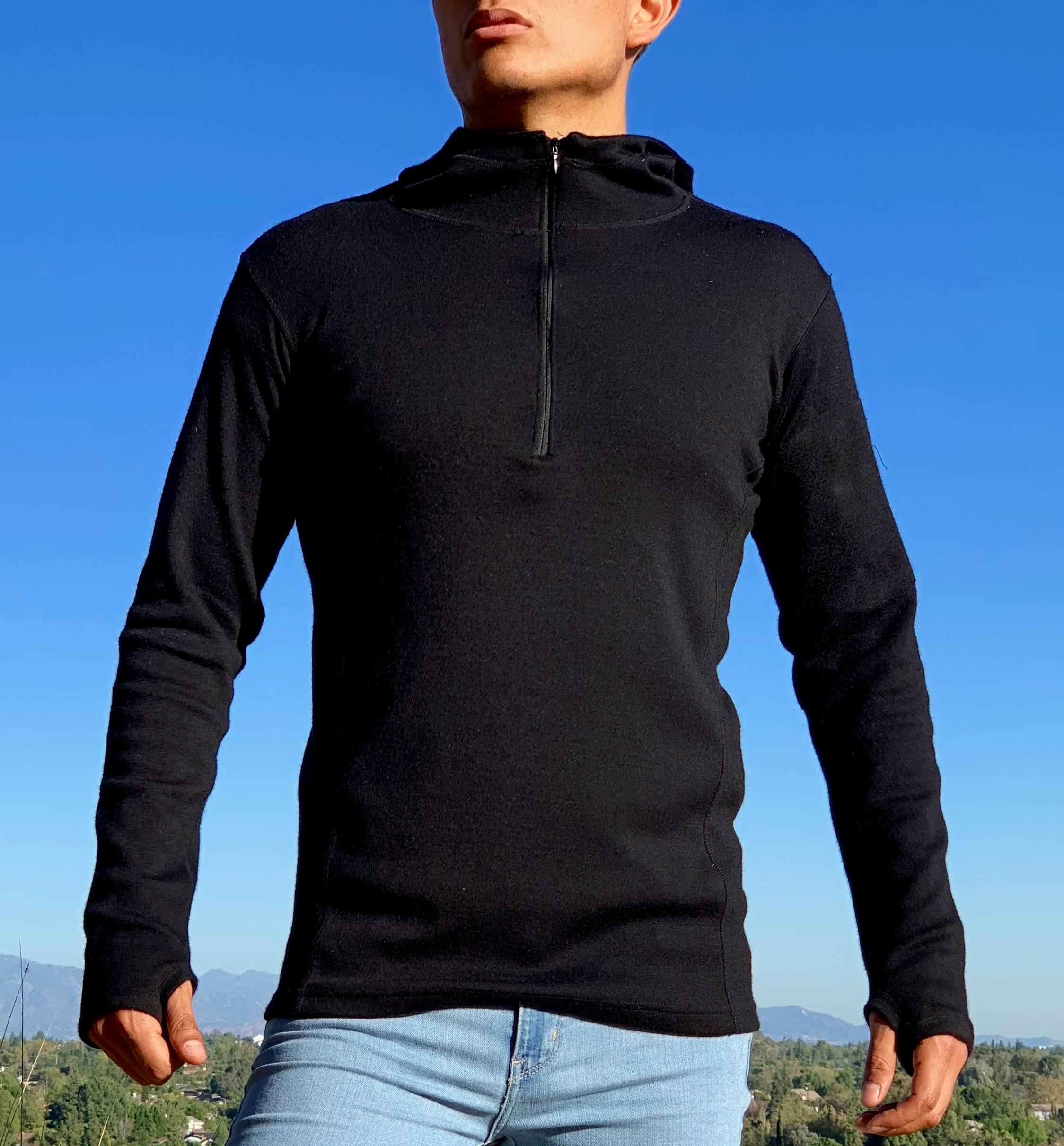 Front view of man wearing alpaca wool fleece hoodie with half zip in black