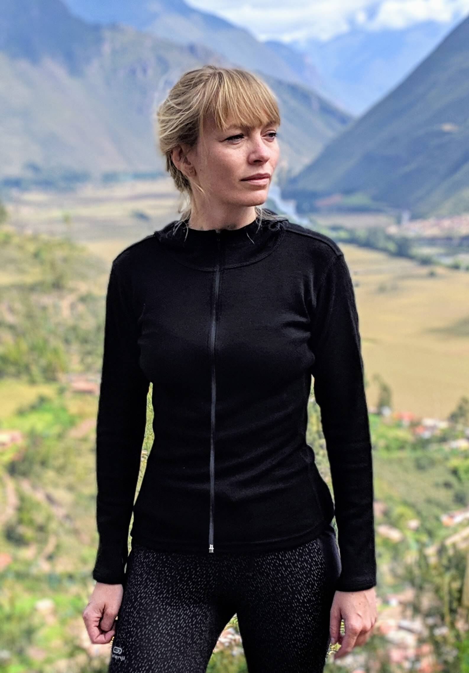Woman wearing alpaca wool base layer with full zip and neck with mountains behind