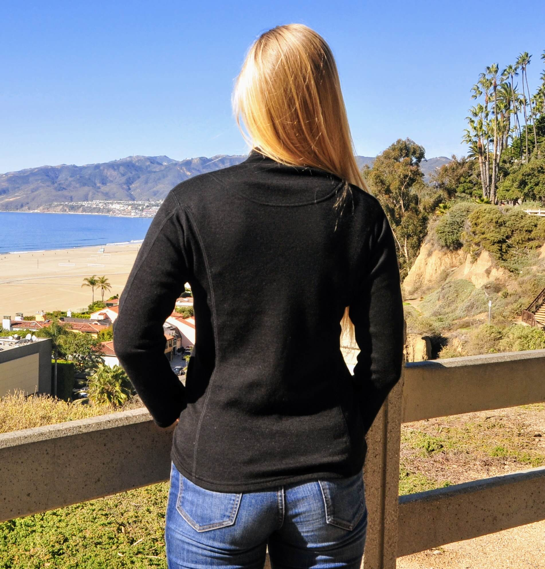 Woman facing beach wearing black alpaca wool base layer with neck
