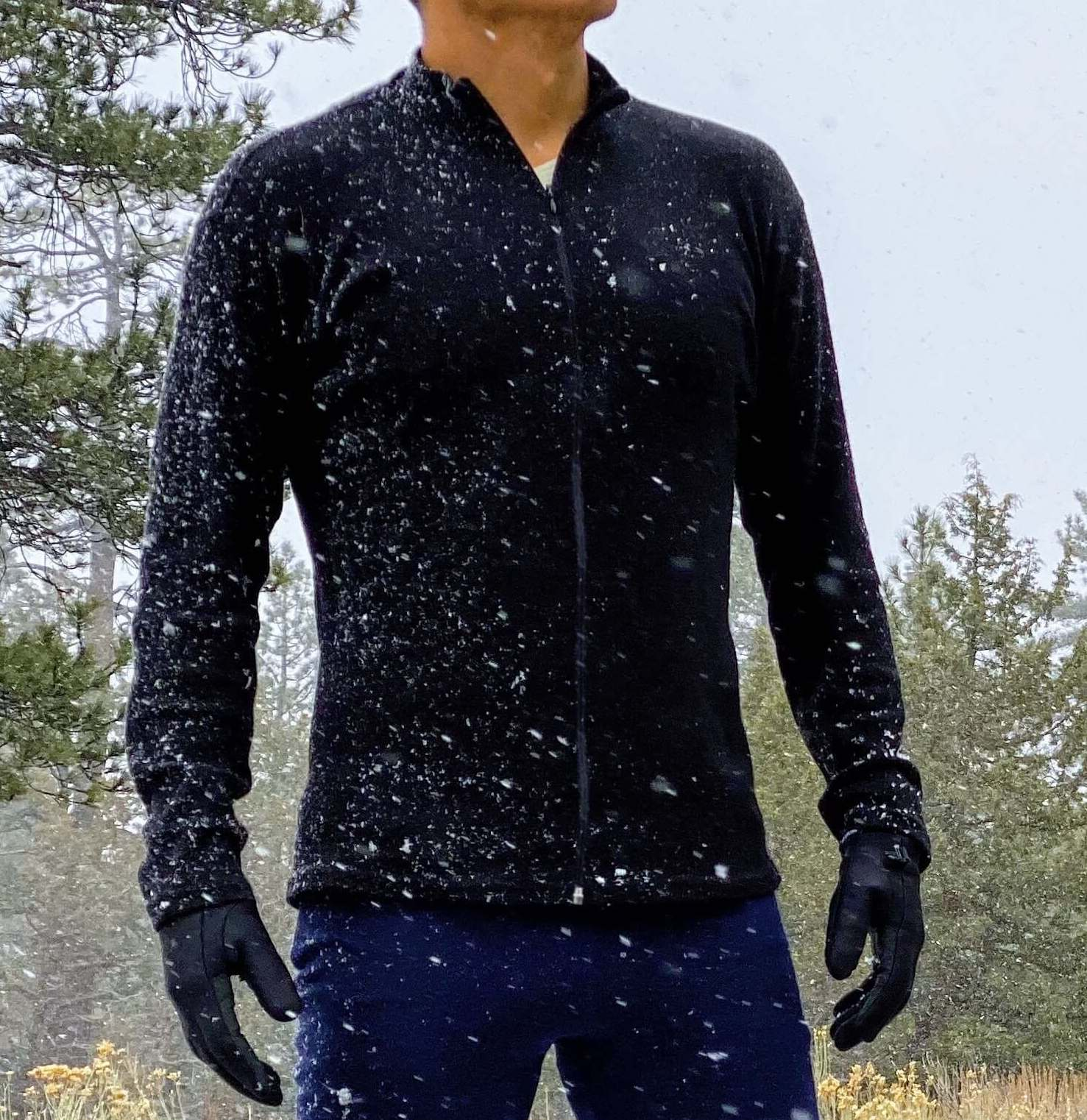 Man wearing alpaca wool base layer full zip neck on a snowy day