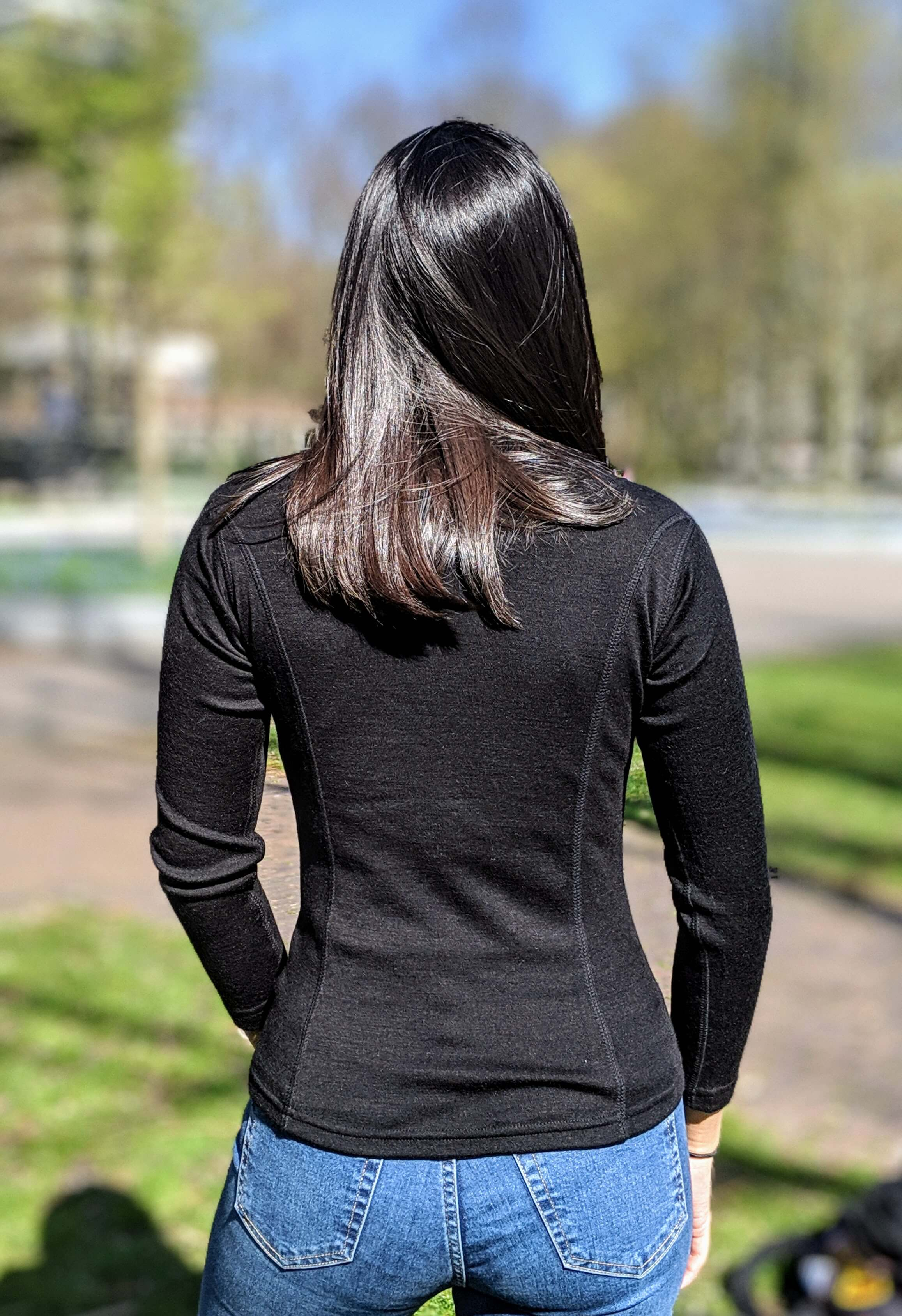 Backside of woman wearing black alpaca wool mid layer in park