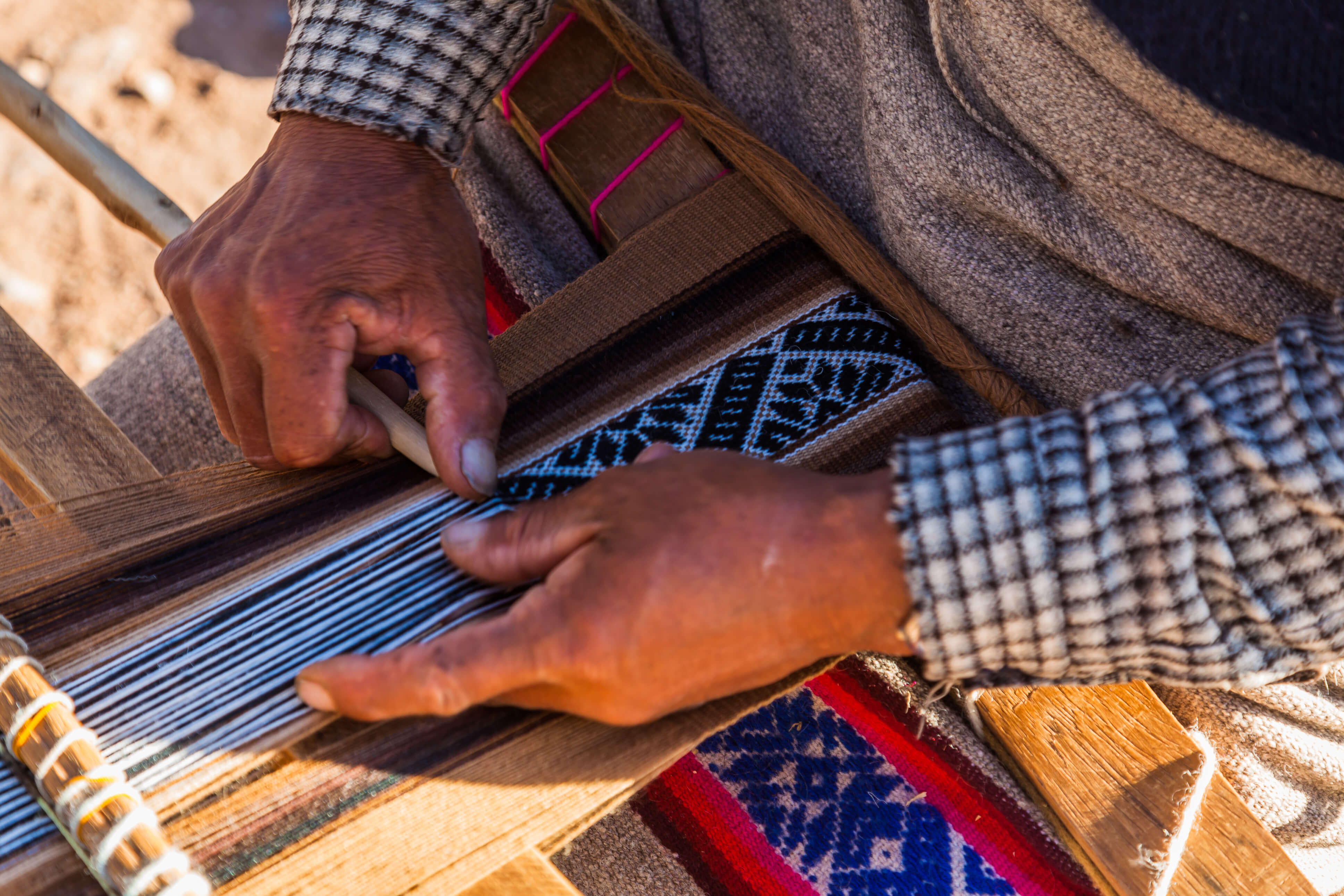 A Woman Weaver Creates an intricate design on her loom