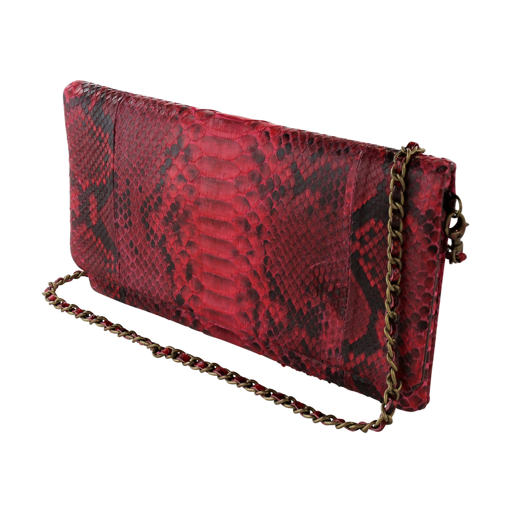 Red  Python snake cross-body clutch that easily doubles as a wallet with the detachable snake braided chain. Magnetic closure. Interior lined in Dumba, distressed ultra-soft leather. Interior zip pockets with compartments for storing cards.