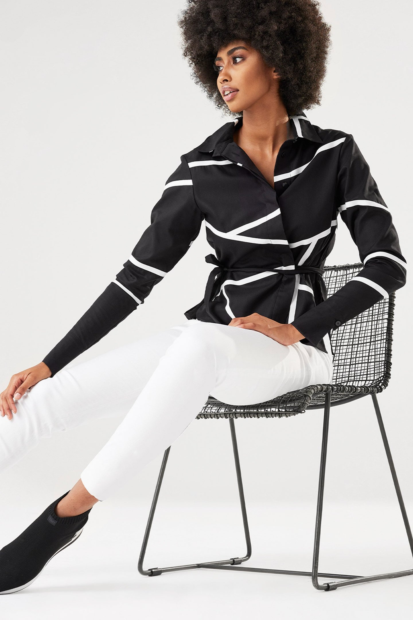 Modern, dynamic and versatile. Meet this season's take on the classic shirt jacket – the Vice Versa Poplin Button Down Top with Contrast Tape Strokes. This elevated everyday essential is designed with a modern relaxed fit and an edgy high-low rounded hemline for a flattering appearance. A cool menswear-inspired collared neckline adds a structured feel while contrasting tape throughout adds a dynamic avant-garde edge to this classic jacket. Crafted using Anatomie's signature wrinkle-free fabrics, this statem