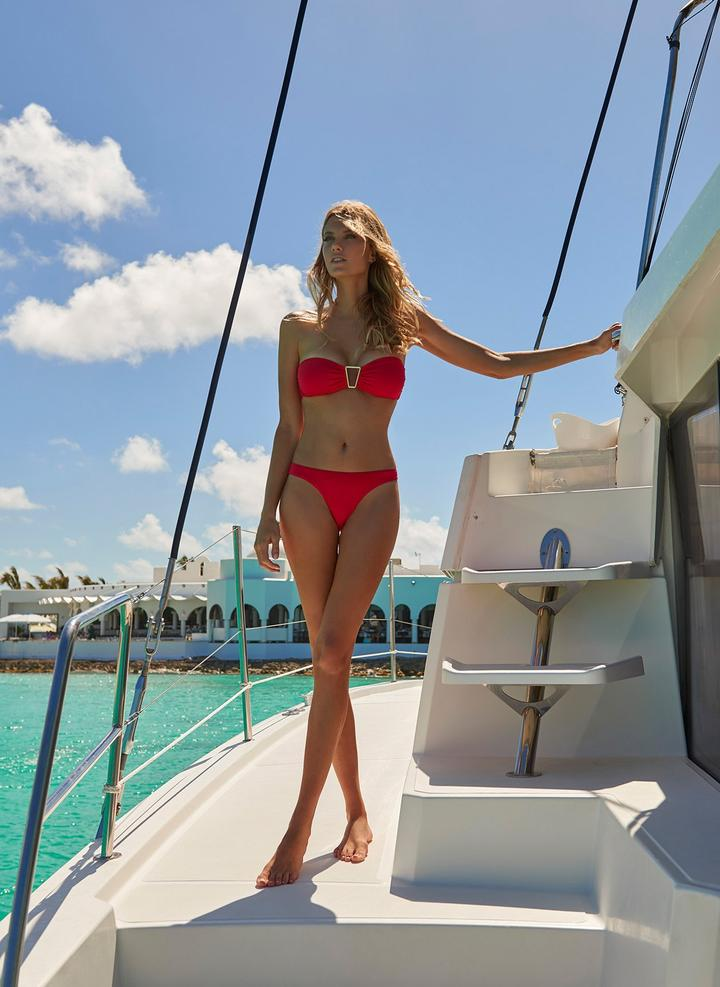 Make a statement in the Barcelona bikini in red. This bold and bright hue will turn heads poolside. Designed with a contemporary golden triangle trim in the center bust to compliment the fiery color, this bandeau bikini also features gentle ruching on the cups and low-rise bottoms to match. Perfect for days spent on the beach improving your tan without the complications of unwanted lines