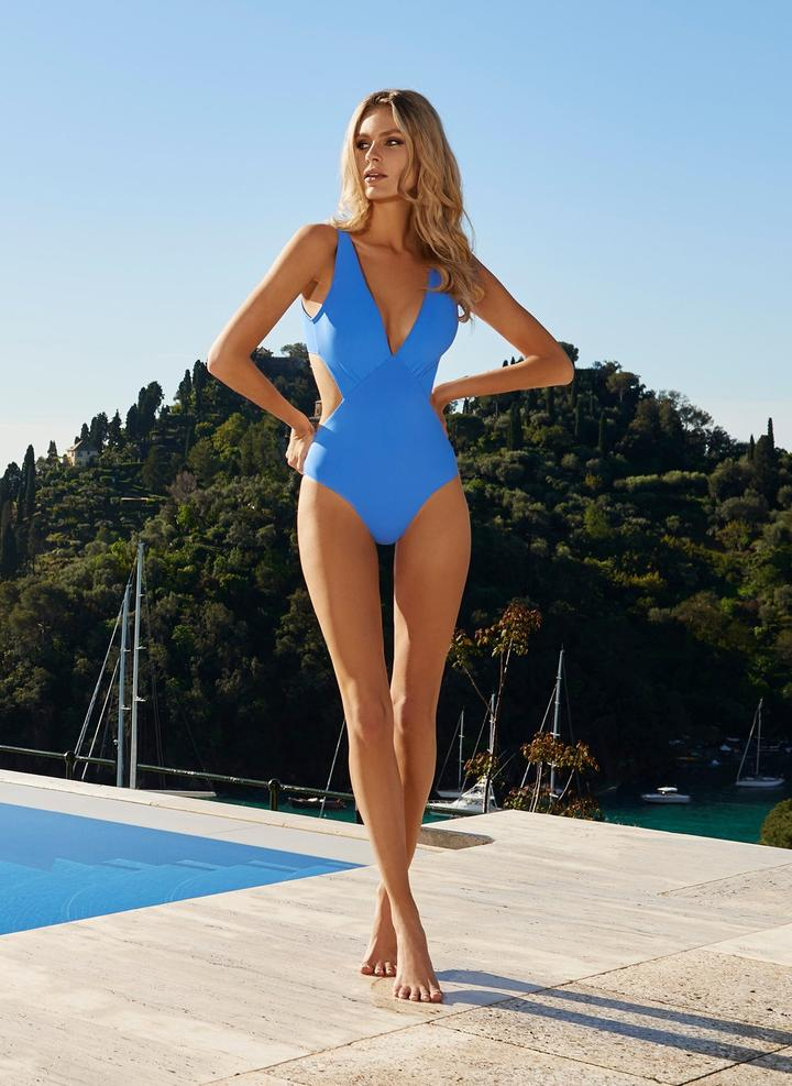 Striking cut-outs and a plunging v-neckline make the Del Mar Swimsuit a statement one-piece that's ideal for lounging poolside. The opulent royal blue hue gives this swimsuit an added touch of luxury. This contemporary swimsuit creates a flattering silhouette to enhance your body's curves. Pair with an Odabash's Pareo for a simple yet stylish ensemble.