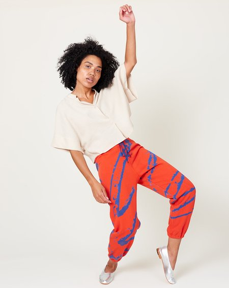 Sweatpants in an orangey-red with strategically placed paint splatter lines on the front and back in blue.