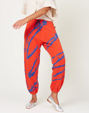 Load image into Gallery viewer, Sweatpants in an orangey-red with strategically placed paint splatter lines on the front and back in blue.