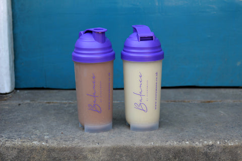 A full shaker of vanilla drink and a full shaker of chocolate drink, sat on a doorstep in front of a blue door