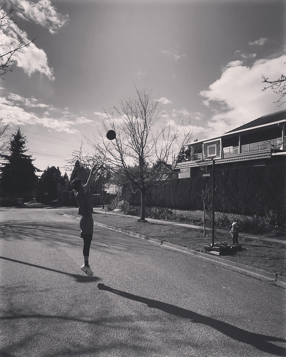 SPITGAN WEBZINE #3 Photo 10. Black and white photo of young man on the street shooting hoops with young toddler watching. Vancouver, BC