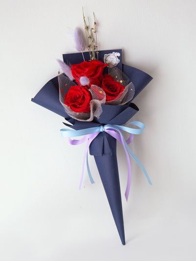 Cone shaped red roses bouquet in navy blue paper