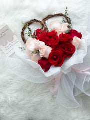 18 red and pink roses with heart-shaped willow branches and a touch of foliages
